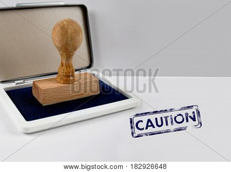 Wooden stamp on a white desk CAUTION