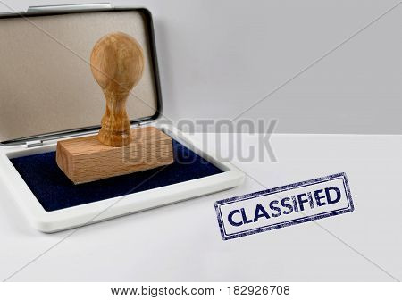 Wooden stamp on a white desk CLASSIFIED