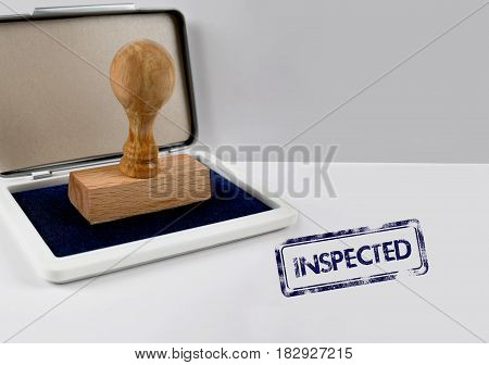 Wooden stamp on a white desk INSPECTED