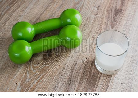 two green dumbbells on the table next to the milk