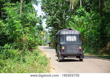 Tuk tuk on road of Sri Lanka, back view