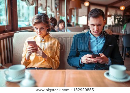 Love couple use their mobile phones in restaurant