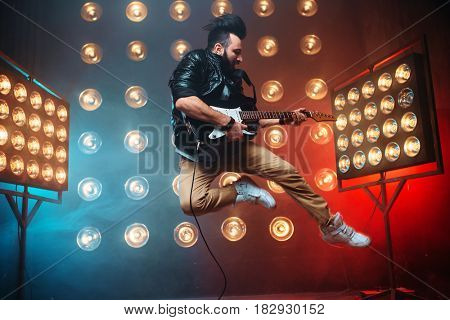 Male performer with electro guitar in a jump