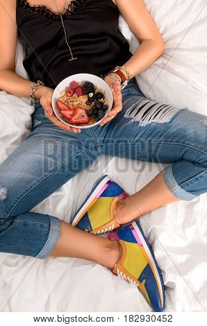 Fashion look. Fashionable woman wearing ripped jeans and black t-shirt with sneakers