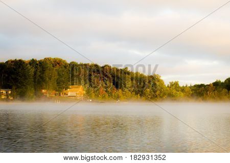 A cottage in the distance on the bank of an open lake in the light of the sunrise.