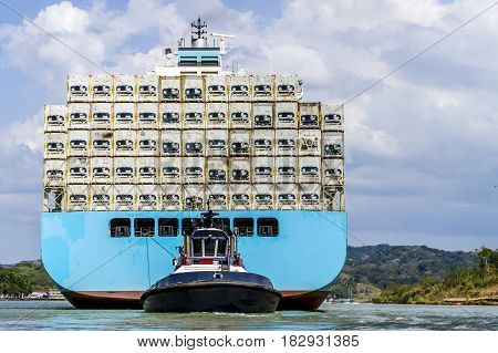 Large cargo ship being guided and towed through the Panama Canal carrying large freights.