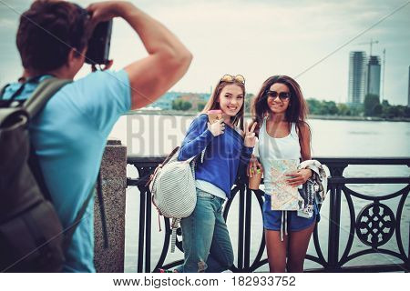 Multi-ethnic friends tourists taking photo near river in a city
