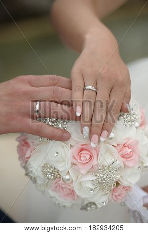 Marriage hands with rings. on the wedding bouquet background