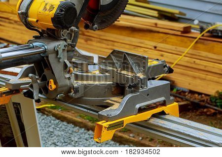 Carpenter Cutting Wooden Plank With Circular Saw Wearing Safety