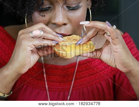 Beautiful African American woman with fancy manicure enjoying sandwich