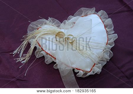 White wedding pillow for rings on brides hands