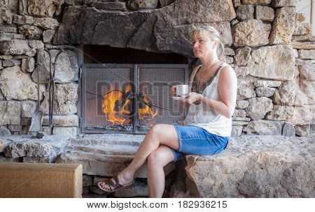 horizontal image of a caucasian woman relaxing by a big old wood burning vintage fire place  drinking a cup of coffee .