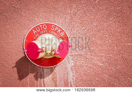horizontal image of a fire hose connector attacked to a stone wall for the fire department.