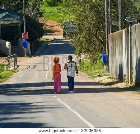 Maun, Botswana - August 28, 2007; Two black children in colorful clothes walking together away on country road in South Africa.