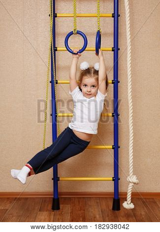 Little girl in sports clothes doing exercises on sports rings on a Swedish wall. The concept of a healthy lifestyle from a young age. Children sport.