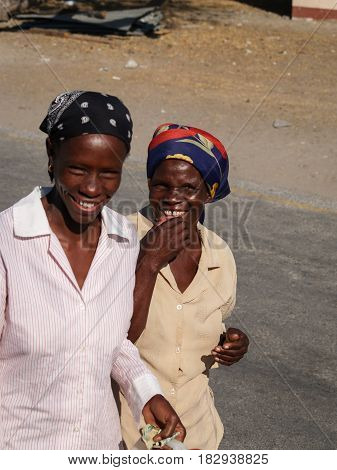 Maun, Botswana - August 28, 2007;Two ethnic African woman laughing as the walk along village road in light colored clothing and headscarves.