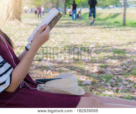 Women read and listen to music under the tree.