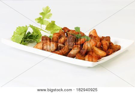 Thai's style deep fried pork belly side pork served with vegetable on a white plate white background.