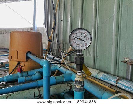 pressure gauge and water-pipe in industrial factory.