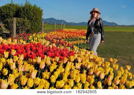 Young smiling woman in garden by tulip beds. Skagit Valley Tulip Festival. Seattle. Mount Vernon. WA. United States.