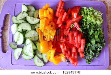 Sliced cucumbers, red and yellow tomatoes and dill