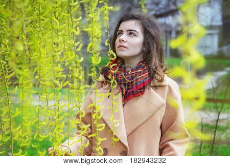 Beautiful teen girl, wearing trendy oversize beige coat and colorful scarf, standing in a spring park near blooming weeping willow tree