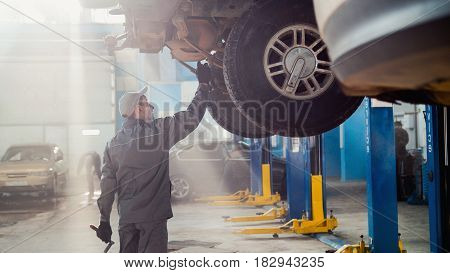 Garage automobile service - a mechanic checks the transmission, wide angle