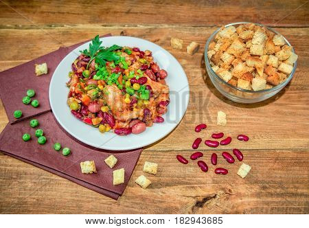Homemade Stewed beans with chicken meat green peas and vegetables served with cut green onion and parsley on a white plate and croutons on wooden table