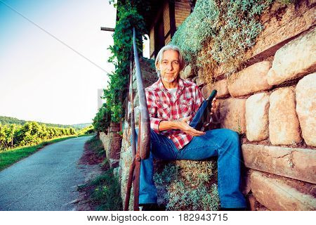 winemaker sitting by his cottage, showing a bottle of self-made wine.