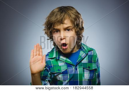 Portrait of angry boy with hand up yelling isolated on gray background. Negative human emotion, facial expression. Closeup.