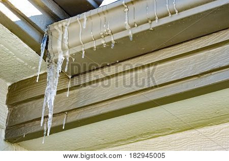 Icicles hanging off the gutters of a roof .