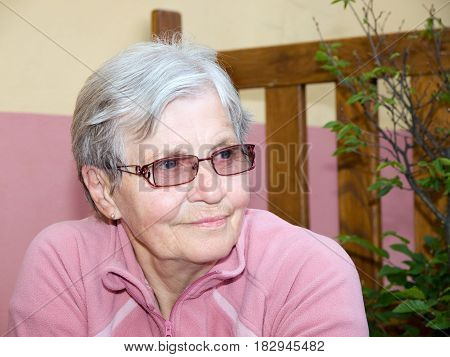 Happy old woman with modern glasses in pink tshirt