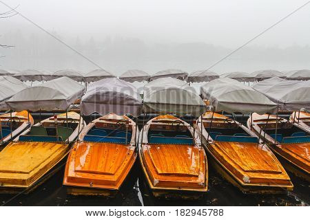 China, Hangzhou, boats on the West Lake in the fog. Many boats waiting for tourists on a misty lake