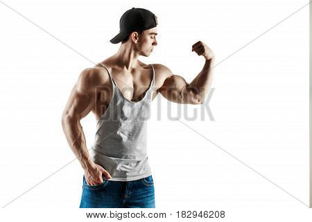 muscular super-high level handsome man in baseball cap and tank top posing on white background