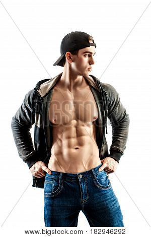 muscular super-high level handsome man in baseball cap posing on white background. showing his six pack press