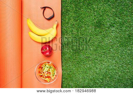 Set of food for sports and bracelet for sports concept on grass background place for inscription