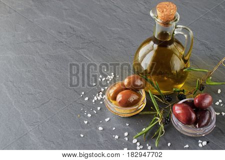 Grey abstract background with glass jar with olive oil and bowls with olives, sea salt and olive branch