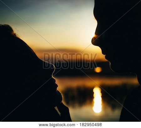 Close-up of beautiful emotional bride young woman holding face of handsome groom young man. Silhouettes of newlywed couple looking into each other eyes family portrait