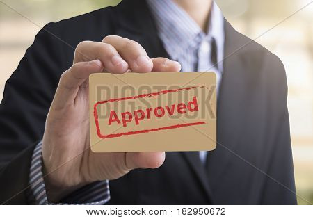 Businessman holding paper writed approved. The flowchart is approved QC and policy for sign symbol passed.