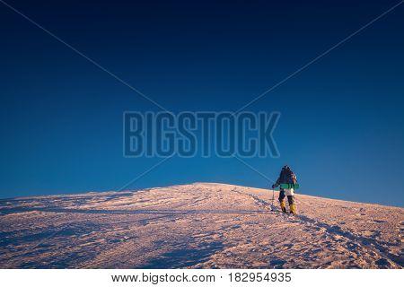 A climber climbs up a snowy to the mountain top. Sunset sky on a horison.