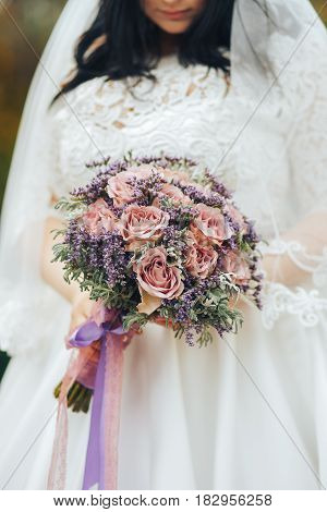 Bride in white dress holding a beautiful wedding bouquet in hands