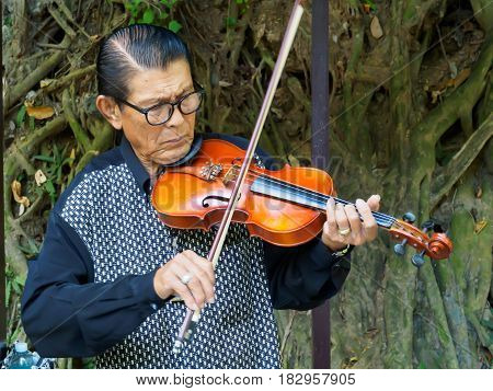 Kanchanaburi, Thailand - December 25,2516 : Asian musician violinist playing violin in public park.