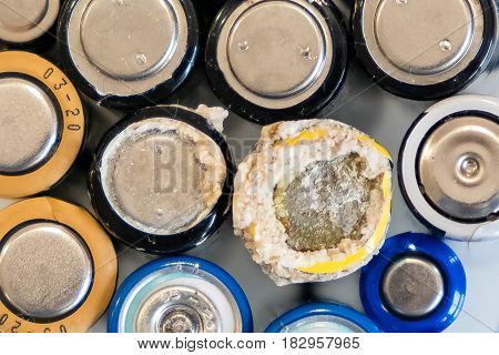 old battery was leaking, hazardous waste. abstract background of colorful batteries. . Alkaline battery aa size. Group of used disposable drain batteries of various size ready