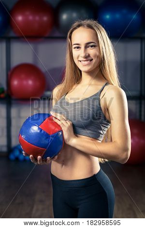 Young smiling fitness girl standing with medicine ball in gym. Warm color toned image