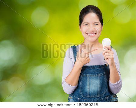 asian woman wearing jumpsuit holding light bulbs