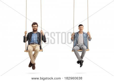 Father and son sitting on wooden swings and looking at the camera isolated on white background