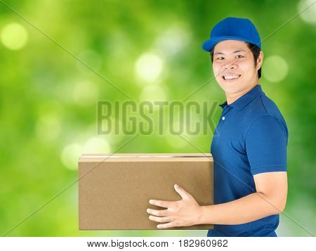 asian delivery man holding carton box with green background