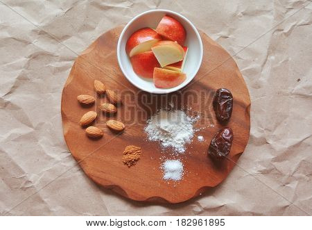 Apple pie recipe ingredients on a wooden board. Apple chunks in the bowl, flour, sugar, cinnamon, dates and almonds.
