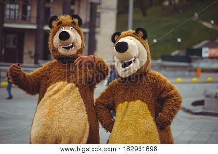 two men in a bear costume in the city in day of protection of animals festive entertainment