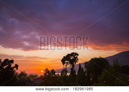 Colorful sunset over coastal town with mountain on background